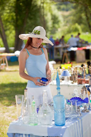 bric: Attractive young woman in a summer sunhat buying antique collectibles at an outdoor stall at an open-air fair or market, browsing through glassware on a table in a park in Provence, France
