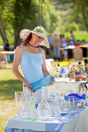 bric: Attractive woman in a large floppy sunhat shopping for antiques and collectibles at an outdoor market and holding a large blue glass bottle in her hands in Provence, France