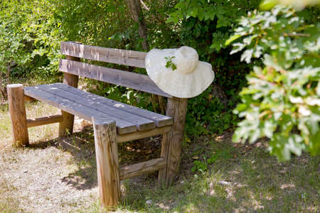 garden bench: Wide brimmed summer sunhat draped over the back of a rustic wooden garden bench standing amongst green foliage in a garden in Provence, France