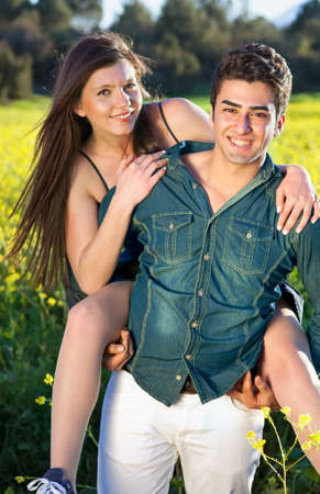camaraderie: Playful affectionate attractive young couple enjoying a day in the summer sun in the country as the young man gives his girlfriend a piggy back as they smile happily at the camera