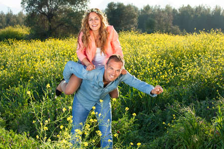 frolic: Playful loving young couple riding piggy back as they frolic around in a colorful yellow field of rapeseed on a sunny summer day Stock Photo