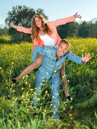貯金箱に乗って幸せな活気のある若いカップル バック彼らの腕を振っていると黄色の菜種のフィールドでの農地に、リラックスした日を楽しむ彼ら