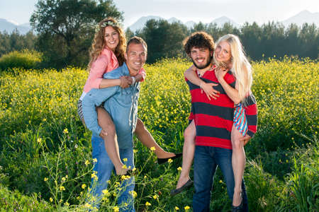 piggy back: Happy young couples enjoying nature as the two smiling young men give their attractive girlfriends a piggy back ride through a yellow rapeseed field Stock Photo