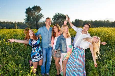 微笑し、笑う彼らが広げた腕と共にグループとしてカラフルな黄色い菜の花でポーズをとって幸せなトレンディな若い人たちのグループ 写真素材