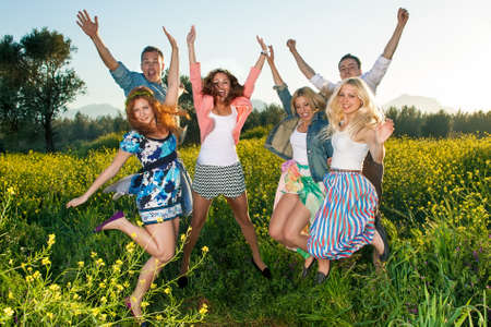 Group of excited young people leaping in the air and celebrating a beautiful hot sunny summer day as they enjoy an outing into the countryside in a colorful yellow rapeseed field Stock Photo