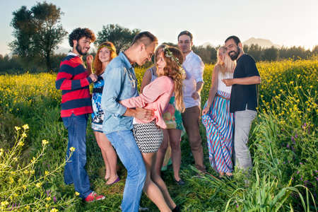 high spirited: Young couple dancing, kissing and having fun watched by a group of their friends as they all enjoy an evening in the countryside