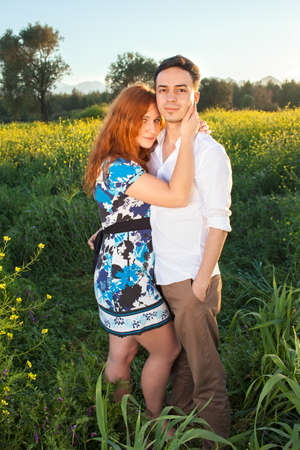interrupted: Affectionate young couple in the countryside standing in a field of yellow rapeseed with the girls arms around her boyfriends neck as though interrupted in a kiss, both looking at the camera