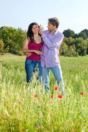 courting: Loving young couple in a poppy field laughing and smiling as the young man puts a red poppy flower in his girlfriends hair as they stand in the summer sunshine