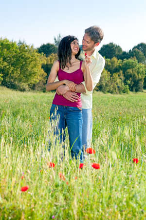 courting: Happy romantic young couple in a poppy field standing in a close embrace looking tenderly into each others eyes in the summer sunshine