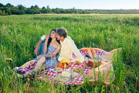 intimately: Romantic couple enjoying a summer picnic sitting on a red and white checkered rug in a poppy field eating their meal while leaning intimately against each other