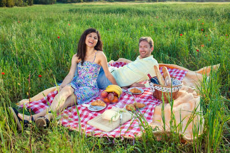 vivacious: Laughing vivacious couple on a summer picnic sitting on a red and white checked rug in a country field enjoying the warm sunshine and freedom of nature