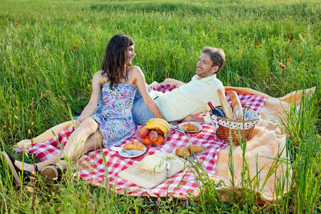 courting: Relaxed young couple enjoying a summer picnic as they sit smiling and chatting on a red and white checked rug in a grassy country meadow