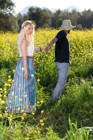 camaraderie: Young man leading his beautiful, young blond girlfriend through a field of colorful yellow rapeseed