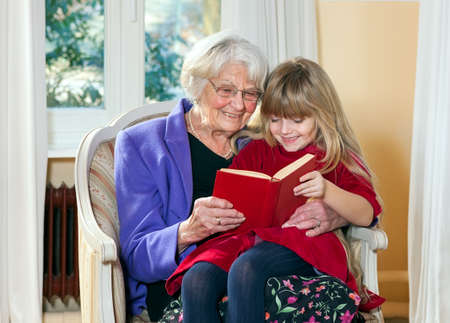 contented: Grandmother and Young Girl Reading together having fun.