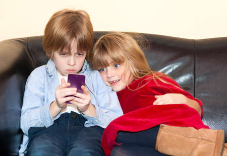 frowning: Little boy reading a text message on a smartphone with a long face as his pretty little sister snuggles up looking over his shoulder with a smile as they relax on a sofa Stock Photo