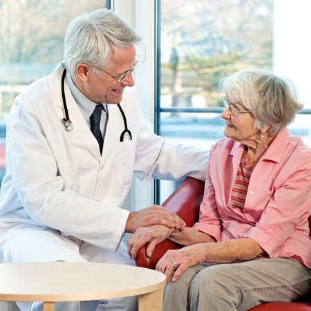 empatia: Anciana en consulta con su médico sentado a hablar con él en un sillón delante de una ventana sonriendo a su acercamiento amablemente simpático Foto de archivo