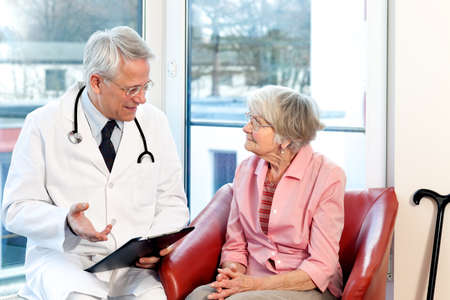 consultant physicians: Male doctor in consultation with a senior female patient sitting having a discussion and offering a detailed explanation as they chat in front of a window in the hospital