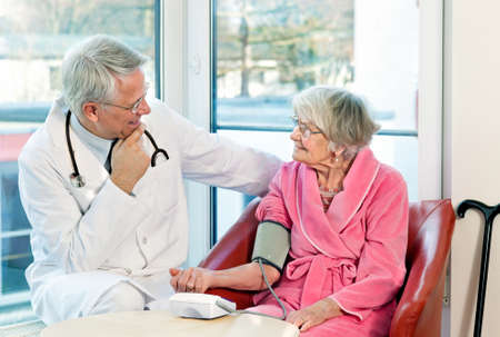 blood pressure cuff: Doctor taking an elderly womans blood pressure with a sphygmomanometer or pressure cuff as they sit talking during a consultation in the clinic Stock Photo