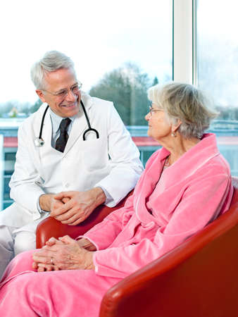 Friendly senior male doctor chatting to an elderly woman patient sitting in her pink dressing gown, smiling as they discuss her prognosis and treatment photo