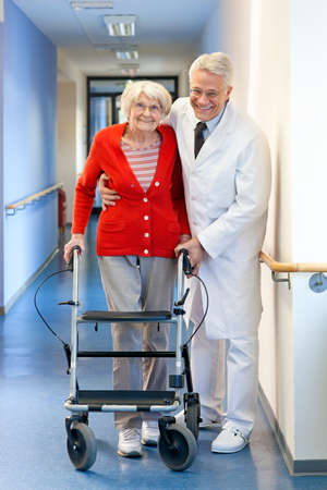 recuperating: Physician helping a senior woman in a walker supporting her with an arms around her shoulders as he assists her with the walking frame
