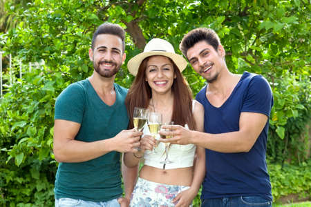 camaraderie: Three smiling friends celebrating with champagne standing arm in arm with the beautiful trendy young woman in the centre between two handsome men in a lush leafy green park
