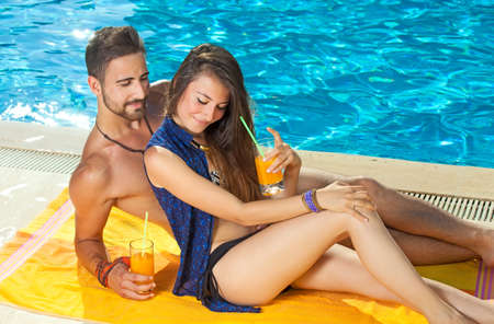 Young couple sunbathing and drinking orange cocktails at the edge of a sparkling blue sunlit pool as they enjoy their summer vacation at a tropical resort photo