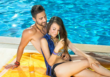 Romantic attractive tanned young couple drinking cocktails at the swimming pool relaxing on a colourful yellow towel leaning against each other in their swimsuits enjoying a tender moment photo