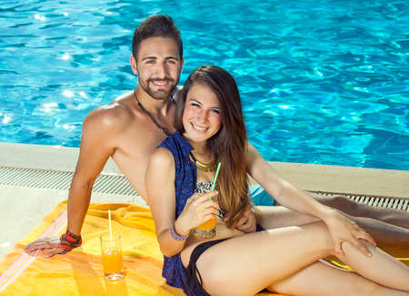 Beautiful happy couple relaxing with orange cocktails alongside a sparkling blue pool as they enjoy the summer sun in their swimsuits soaking up a tan looking at the camera with friendly smiles photo