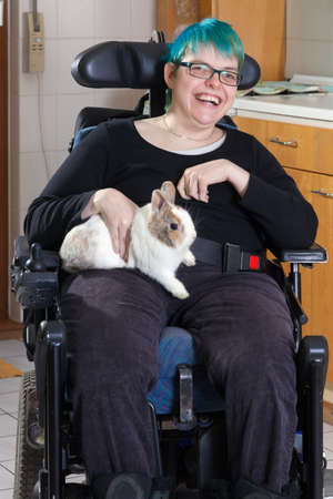 Cheerful young infantile cerebral palsy patient caused by complications at birth sitting in a multifunctional wheelchair stroking a pygmy rabbit as therapy with a beaming smile