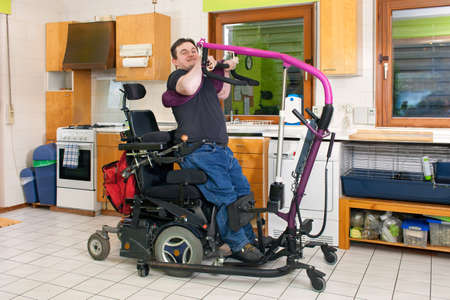 maneuver: Spastic young man with infantile cerebral palsy caused by birth complications using a patient lift to maneuver himself into a multifunctional wheelchair for mobility Stock Photo