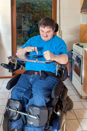 Spastic young man confined to a multifunctional wheelchair as a result of infantile cerebral palsy caused by birth complications