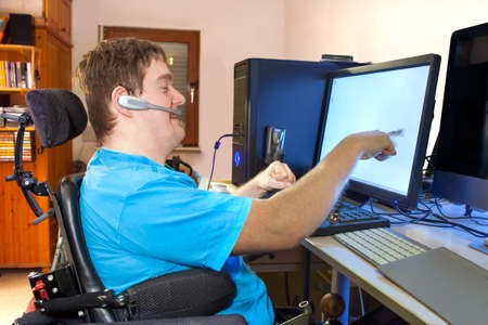 Spastic young man with infantile cerebral palsy caused by a complicated birth sitting in a multifunctional wheelchair using a computer with a wireless headset reaching out to touch the touch screen 스톡 콘텐츠