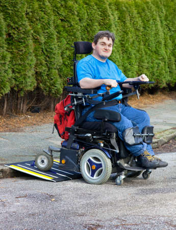 Mobility for infantile cerebral palsy patients caused by birth complications with a spastic young man in a multifunctional wheelchair negotiating a mobile ramp on a kerb during an integration outing