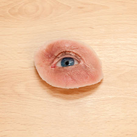 eye socket: Synthetic Eye and Skin for Destroyed Eye Sockets, on Wooden Table. Also Used for Films.