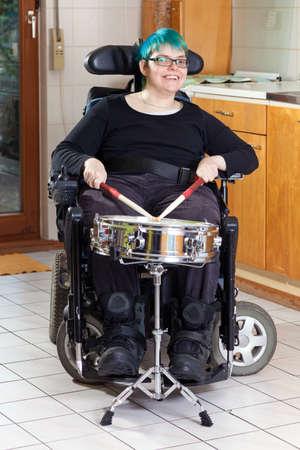 Gelukkig spastische jonge vrouw met infantiele cerebrale parese als gevolg van complicaties bij de geboorte beperkt tot een multifunctionele rolstoel slaan op een trommel, als onderdeel van haar therapie lachend naar de camera