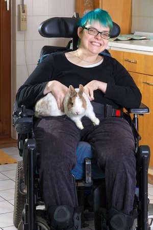 Jonge vrouw met infantiele cerebrale parese als gevolg van de geboorte complicaties beperkt tot een multifunctionele rolstoel strelen een dwergkonijn als onderdeel van haar therapie geven de camera een charmante glimlach