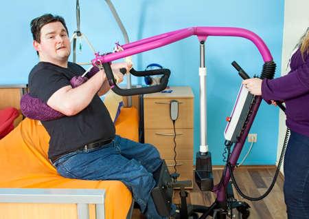 Spastische jongeman met infantiele hersenverlamming veroorzaakt door complicaties bij de geboorte met behulp van een tillift om zichzelf te hijsen van een verpleegbed voor overdracht naar een multifunctionele rolstoel Stockfoto