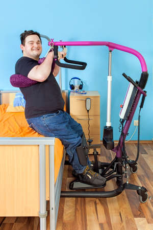 complications: Spastic young man with infantile cerebral palsy from birth complications using a patient lift to transfer from a healthcare bed to his wheelchair giving the camera a happy friendly smile Stock Photo