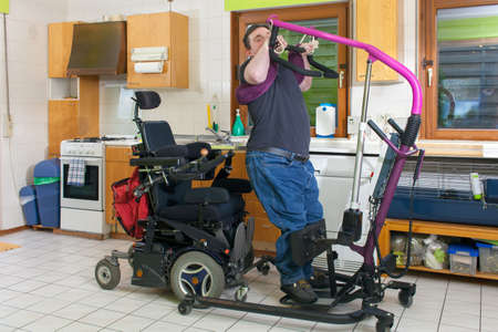 cerebral palsy: Young man with infantile cerebral palsy from birth complications using a patient lift to move from his bed to a multifunctional wheelchair Stock Photo