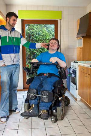 Jonge spastische mannelijke infantiele cerebrale parese patiënt veroorzaakt door complicaties bij de geboorte zitten in een multifunctionele rolstoel luisteren naar muziek op de koptelefoon geholpen door een verzorger die lacht met plezier