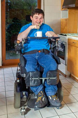 Spastische jongeman met infantiele cerebrale parese veroorzaakt door complicaties bij de geboorte zitten in een multifunctionele stoel genieten van een mok van drank drinken door een rietje Stockfoto