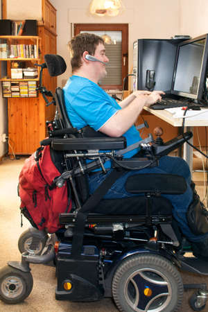 Man with spastic infantile cerebral palsy caused by a complicated birth sitting in a multifunctional wheelchair using a computer with a touch screen and wireless headset, side view