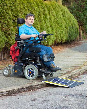 autonomia: Joven con parálisis cerebral infantil causada por complicaciones en el parto negociar una rampa móvil en un bordillo de carretera con su silla de ruedas multifuncional durante una excursión de día para la integración