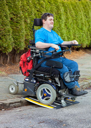 kerb: Spastic young man with infantile cerebral palsy caused by birth complications using a mobile ramp on a kerb to drive onto the road with his multifunctional wheelchair during an outing for integration Stock Photo