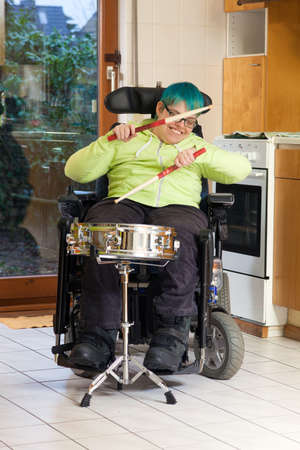 Young woman with infantile cerebral palsy caused by complications at birth sitting in a multifunctional wheelchair playing a drum for spastic therapy with a happy smile Standard-Bild