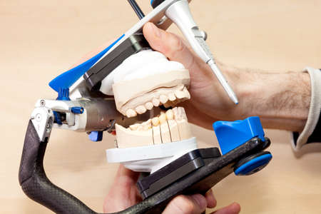 dentition: Designing Artificial Facial Dental on Device, Isolated on Wooden Table.