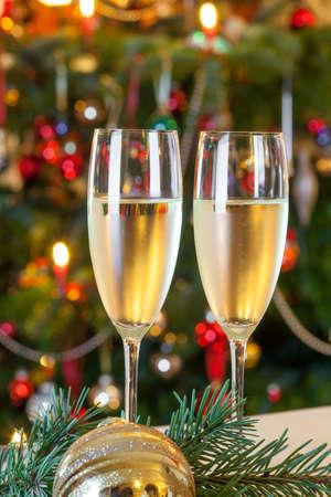 Glasses of champagne and candles: Thành phần với đồ trang trí Giáng sinh và hai ly rượu sâm banh, cây Giáng sinh với nến sáng trong nền. đồ trang trí.