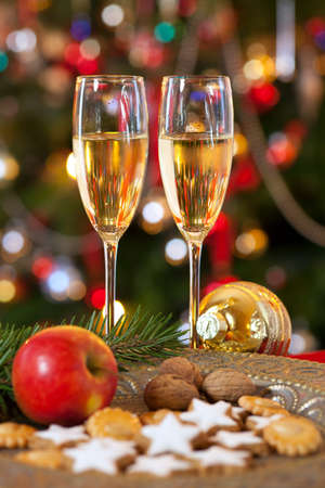 solemnity: Christmas decoration still life concept with glasses of champagne for two persons, beautiful decorated Xmas tree at home. Stock Photo