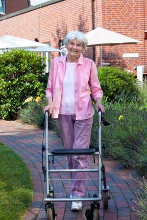 Gelukkig oudere vrouw met behulp van een loophulpmiddel staande op een verharde weg lachen naar de camera Stockfoto