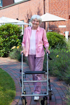 Happy elderly woman using a walking aid standing on a paved pathway smiling at the camera